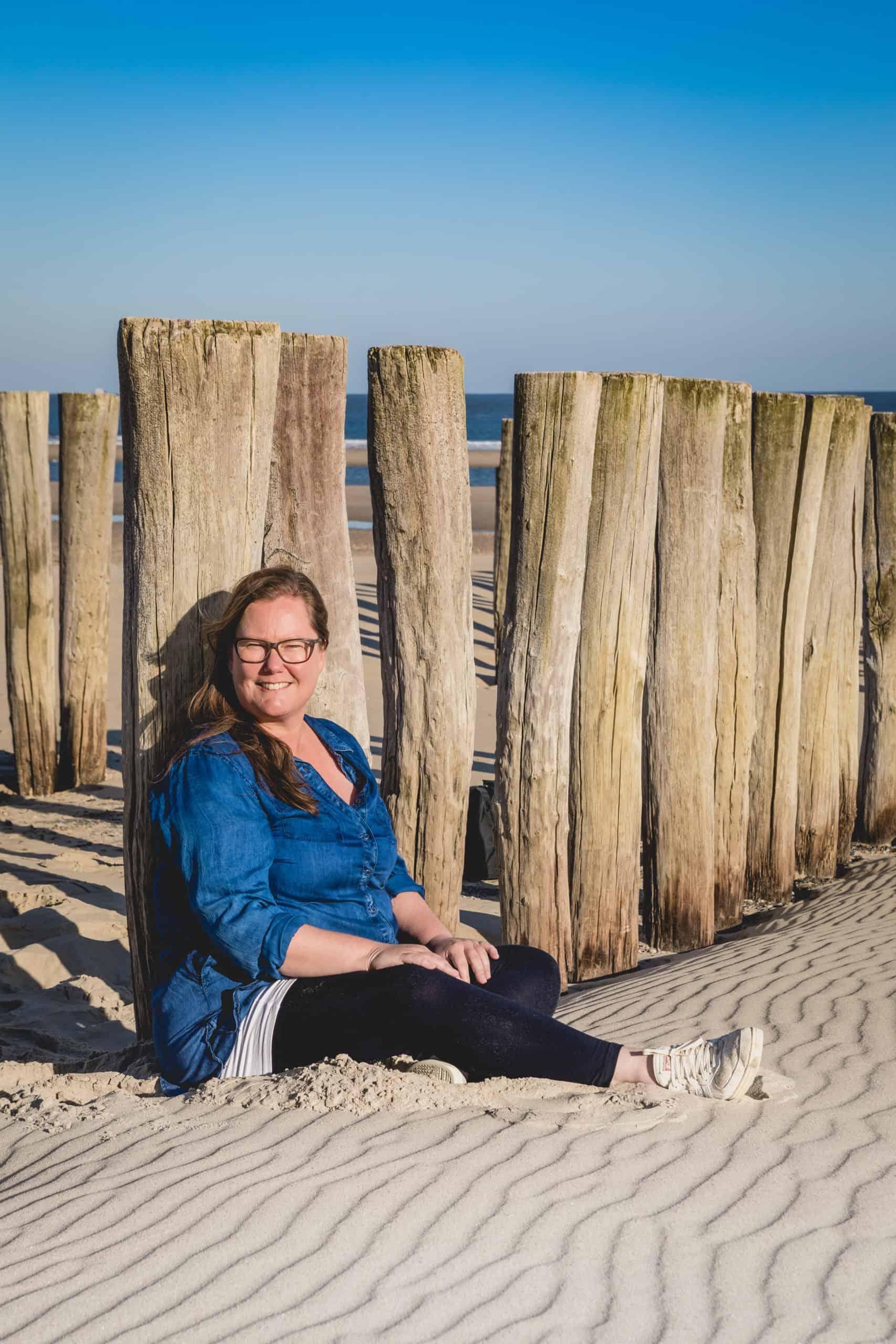 Caja ontspannen zittend op het strand. Tegen de starndpalen. Ze kijkt je aan.